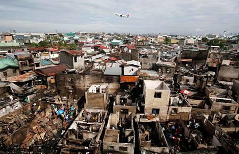 Lentokone lensi tulipalon vahingoittaman asuinalueen yli Manilassa, Filippiineillä.