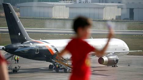 Lapsi leikki maanantaina Maltan lentokentällä. Taustalla Titan Airwaysin kone, joka on ollut Thomas Cookin asiakkaiden käytössä.