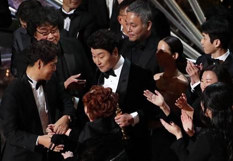 Bong Joon-ho (ylh.vas.) ja työryhmäänsä juhlimassa voittoa Oscar-gaalan lavalla.