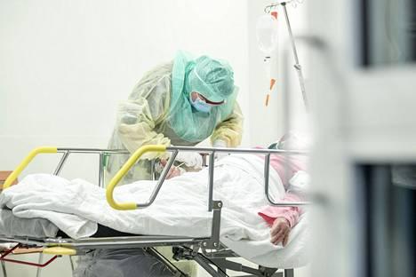 Suojavarustukseen pukeutunut hoitaja otti näytteen koronaepäillyltä Turun yliopistollisessa keskussairaalassa huhtikuussa.