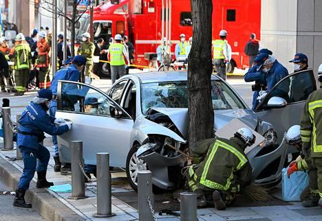 Poliisit tutkivat autoa onnetomuuspaikalla Nagoyan kaupungissa Japanissa.