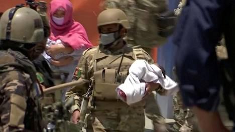 Afganistanin turvallisuusjoukkojen sotilas kantoi vauvaa turvaan hyökkäyksen kohteeksi joutuneesta sairaalasta Kabulissa tiistaina.