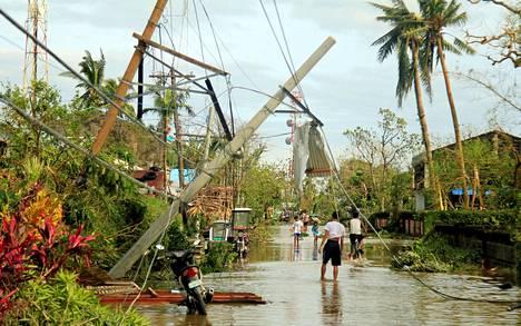 Asukkaat kahlasivat taifuunituhojen keskellä Malinaossa maanantaina.