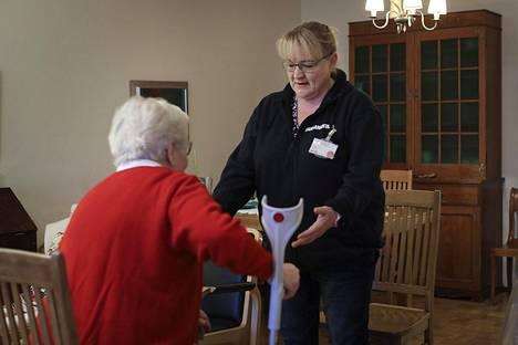 Sairaanhoitaja Anu Kontula käy asiakkaansa kanssa läpi jumppaliikkeitä. Aivan ensimmäisenä noustaan tuolilta istumaan, hoitaja vierellä turvana.