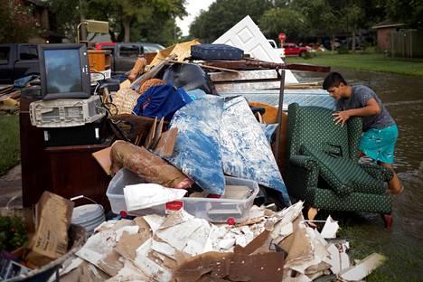 Isaac Zermeno kantoi huonekaluja pois tulvavesien valtaamasta naapuritalosta Houstonissa Yhdysvalloissa sunnuntaina.