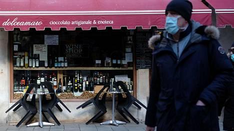 Mies kulki suljetun kahvilan ohi Venetsiassa sunnuntaina.