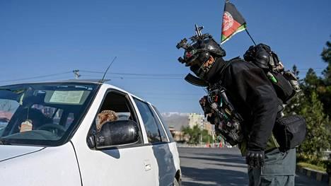 Turvallisuusjoukkojen työntekijä tarkasti autoilijoita tiesululla Kabulissa sunnuntaina.