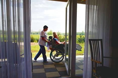 """Vanhustenhoitaja työntää Helga Schröteriä pyörätuolissa saksalaisessa vanhainkodissa Puolassa. Vanhainkoti on tuliterä. Schröter muutti Puolaan Wuppertalista Länsi-Saksasta. """"Myös Saksassa hoito oli hyvää, mutta se tuli liian kalliiksi"""", hän perustelee muuttoaan."""