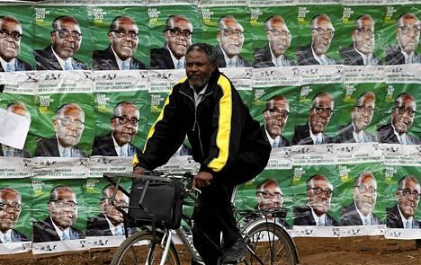 Mies pyöräili Robert Mugaben vaalijulisteiden ohi Hararessa.