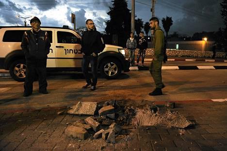 Israelilaiset sotilaat ja siviilit seisoivat Gazasta laukaistun raketin aiheuttaman kuopan vieressä Sderotin kaupungissa Israelissa.