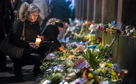 Nainen toi kukkia terrori-iskun uhrien muistoksi Kööpenhaminan synagogan edustalle sunnuntai-iltana.