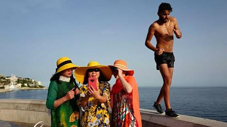 Mies lenkkeili selfieitä ottavien turistien ohi Ranskan Nizzassa maanantaina. Ranskaan on luvattu kuluvalla viikolla jopa 40 lämpöastetta.