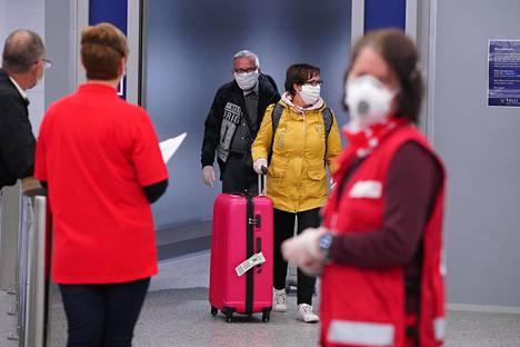 SPR:n työntekijät jakoivat koronatietoa Alicanten-koneesta tuleville matkustajille Helsinki-Vantaan lentokentällä maaliskuussa.