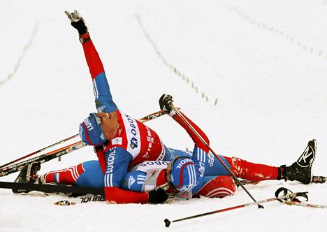 Venäjän Aleksandr Legkov (ylh.) ja Ilja Tšernisov juhlivat voittoaan maastohiihdon maailmancupin 50 kilometrin kisassa Oslossa lauantaina.