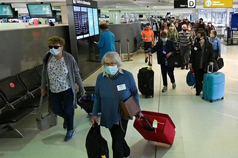 Matkustajat etenivät lähtöselvitykseen matkalla Uuteen-Seelantiin Sydneyn lentoasemalla maanantaina.