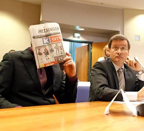 Syytetty piiloutui oikeudessa lehden taakse. Vieressä istuu hänen asianajajansa Kaarle Gummerus.