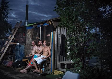Otso Korhonen (vas.), Otso Tuominen ja Deni Haapameri istuivat Sompasaunan takana ja katselivat Kruununhaan maisemaa Sompasaunalla juhannuksena 2017.