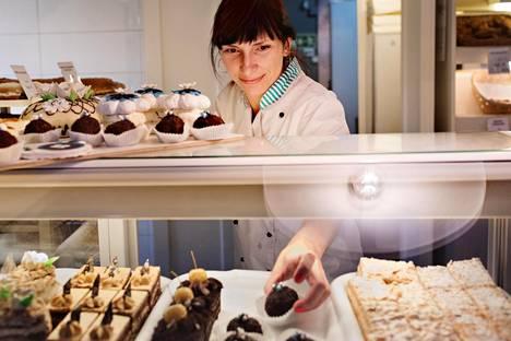 Pagariliisu-leipomon pääkondiittori Kirsti Suviste asettelee Viron värein koristeltuja rummimuna-leivoksia vitriiniin.