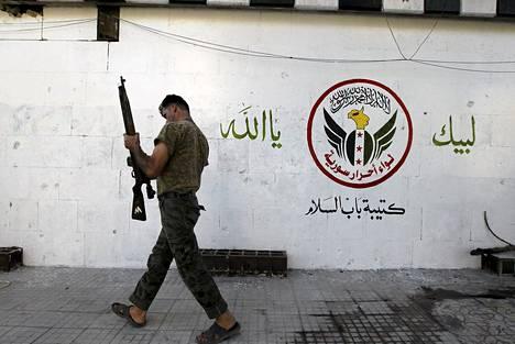 Kapinallistaistelija Sakhourin alueella Aleppossa lauantaina. Seinämaalauksessa lukee: Me olemme sinun, oi Allah.