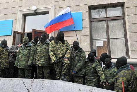 Naamioituneet miehet vartioivat hallintorakennuksen edessä Ukrainan Simferopolissa lauantaina.