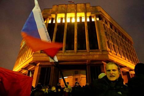 Mies heilutti Venäjän lippua autonomisen Krimin parlamenttirakennuksen edessä Ukrainan Simferopolissa torstaina. Venäläismieliset joukot nostivat Venäjän lipun rakennuksen salkoon.