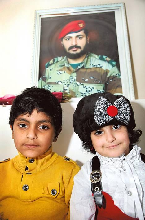 Jemeniläinen sotilas Adnan Al-Qawi (taulussa) tapettiin Yhdysvaltain lennokki-iskulla marraskuussa. Hänen lapsensa Al-Abjar (vas.) ja Alla asuvat nyt isänsä veljen luona.