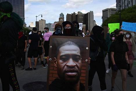Mielenosoittaja kantoi George Floydin kuvaa Detroitissa 29. toukokuuta.