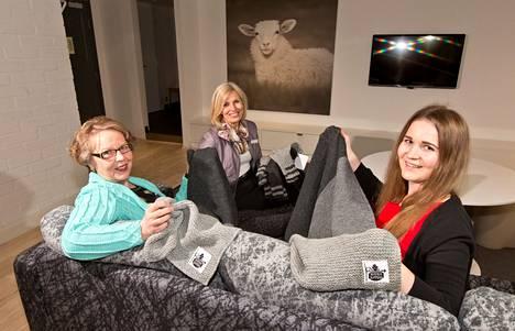 Eläkeläinen Anna-Liisa Vuorinen (vas.), hotellinjohtaja Irmeli Puolanne ja opiskelija Taru Pyylampi esittelevät Hotel Villan käsitöitä.