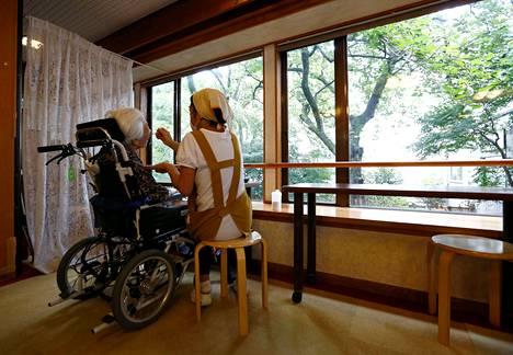 Yksityisen hoivakodin henkilökunnan jäsen hoiti asukasta Tokiossa Japanissa. Kuva vuodelta 2016.