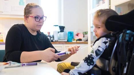 Espoolainen opiskelija ja kahden erityislapsen yksinhuoltaja Jenni Arteli antamassa nuoremmalle lapselleen Kasperille lääkkeet lounaan yhteydessä.