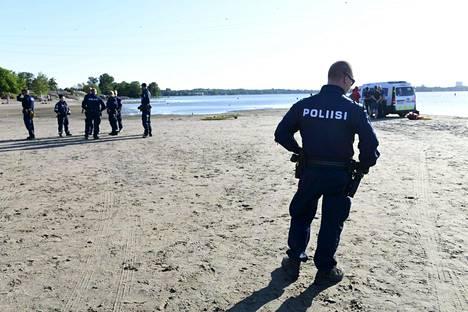 Poliiseja Hietaniemen uimarannalla juhannuspäivän iltana. Yksi kesäkuun hukkumisista tapahtui kyseisenä päivänä.