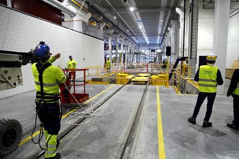 Varikon korjaamohallissa tehdään viimeistelyjä. Keltainen laite on vaunun profilointikone, jossa sorvataan vaunun pyöriä.