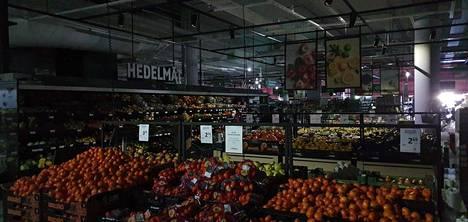Värikkäät hedelmät erottuivat pimenneessä hypermarketissa.