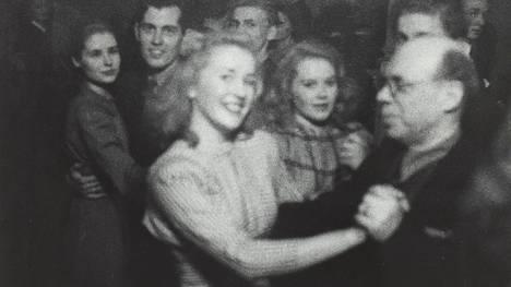 Etualalla Taideteollisen keskuskoulun opettaja Arttu Brummer tanssii vaalean naisen kanssa tuntemattomassa paikassa Helsingissä. Kuvatietojen mukaan valokuvan otti Matti Saanio vuosien 1940 ja 1944 välillä, joten kyseessä olivat laittomat salatanssit. Saaniosta tuli myöhemmin tunnettu valokuvaaja ja taiteilijaprofessori.