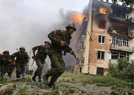 Georgialaisia sotilaita juoksi liekehtivän rakennuksen ohi Venäjän pommittamassa Gorin kaupungissa 9. elokuuta 2008. Venäläiskoneen asuinrakennukseen pudottaman pommin kerrottiin tappaneen ainakin viisi ihmistä.