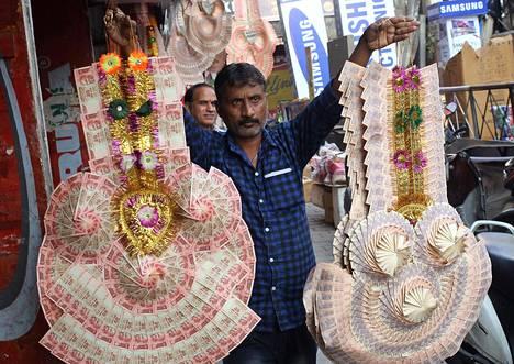 Intialainen kauppias myi pikkuseteleistä tehtyjä koristeita torilla. Pienimpiä seteleitä ei ole poistettu käytöstä, mutta niiden arvo on niin olematon, että niillä on vaikea tehdä suuria ostoksia.
