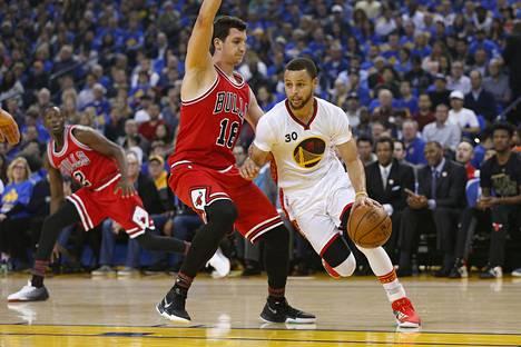 Golden State Warriorsin takamies Stephen Curry (30) kuljetti pallon ohi Chicago Bullsin hyökkääjän Paul Zipserin (16) 8. helmikuuta 2017.