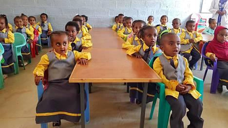 Gergin koulussa esikoululaiset istuvat tiukasti pulpeteissaan ja toistavat opettajan tervehdykset kuuluvasti yhteen ääneen.