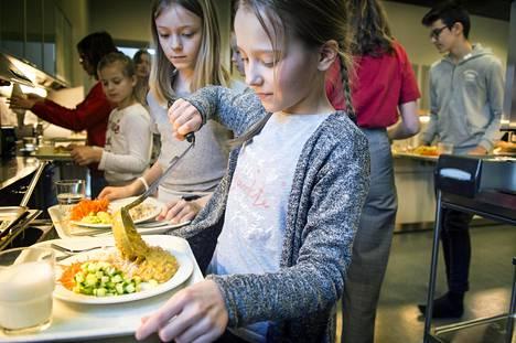 Mea Korhonen ottaa kasvisruokaa Vuosaaren koulussa, Marie Haldén odottaa vuoroaan.