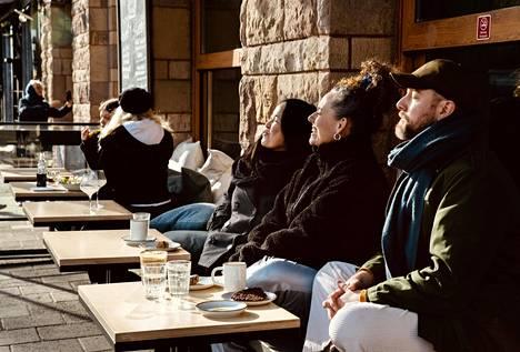 Ihmiset paistattelivat auringossa kahvilan terassilla maanantaina Tukholman Södermalmilla.