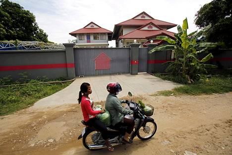 Nainen ohitti moottoripyörällä turvapaikanhakijoiden tilapäisen majoituskeskuksen Phnom Penhissä Kambodžassa.