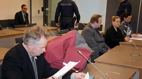 Vakavasti sairaan tytärpuolensa surmaamisesta syytetty mies (toinen vas.) piileskeli takin alla Itä-Uudenmaan käräjäoikeudessa Hyvinkäällä 12. maaliskuuta 2019.