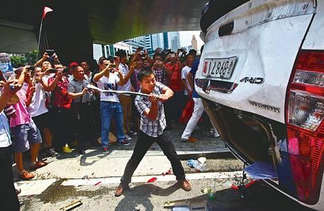 Mielenosoittaja vandalisoi japanilaisvalmisteista poliisiautoa Shenzenissä Kiinassa sunnuntaina.