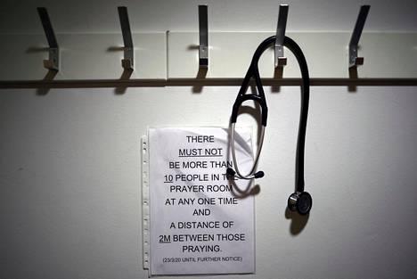 Stetoskooppi oli ripustettu vaatenaulakkoon rukoushetken ajaksi. Koronarajoituksista muistutettiin lapulla.