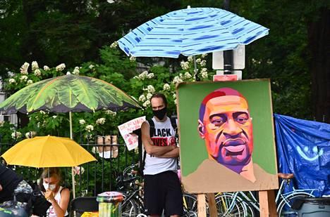 Mielenosoittaja George Floydia esittävän maalauksen vieressä New Yorkissa kesäkuun lopulla.