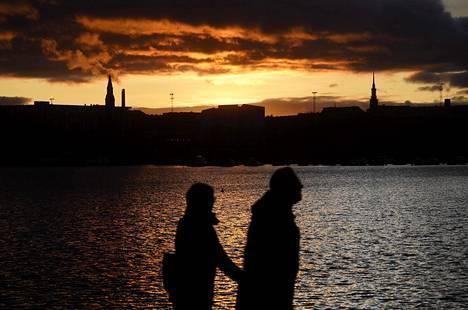 31. lokakuuta: Ulkoilijoita Tokoinrannassa auringonlaskun aikaan.