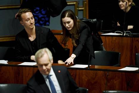 Pääministeri Sanna Marin (sd) painaa läsnäolonappia eduskunnassa maanantaina 30. maaliskuuta. Vieressä Sdp:n Ilmari Nurminen, edessä varapuhemies Antti Rinne (sd).