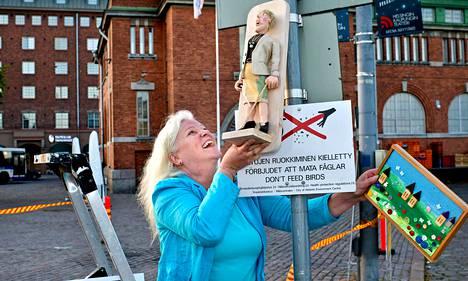 Raija Lehtinen odotteli syntymäpäiväkontteja saapuvaksi Hakaniemen torilla torstaina. Odottamassa oli myös Lehtistä esittävä nappikauppiasnukke.