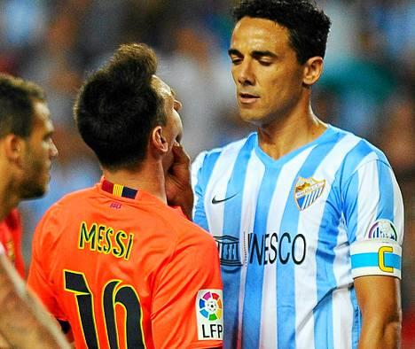 Malagan brasilialaispuolustaja Weligton kimpaantui Barcelonan Lionel Messiin ja nappasi tätä kiinni leuasta.