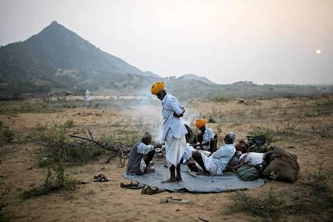 Kamelikauppiaat odottivat ateriansa valmistumista Pushkarin markkinoilla Rajastanissa Intiassa. Markkinoilla myydään ja vaihdetaan tuhansia eläimiä, lähinnä kameleita.